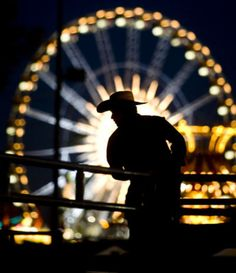 A cowboy is silhouetted against the lights of a Ferris wheel before the start of bull riding at the Arizona State Fair. Photo by Pat Shannahan,