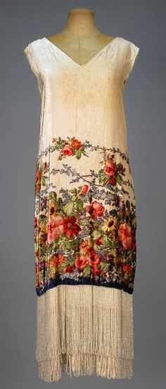 PRINTED VELVET FLAPPER DRESS with BEADED FRINGE, 1920s. Sleeveless ivory silk having polychrome floral printed skirt and looped crystal bead fringe at the hemline, longer underdress having satin hem band with a second band of fringe (Small underarm stains, few tiny holes under one arm, bodice some tiny spots and discoloration) good.