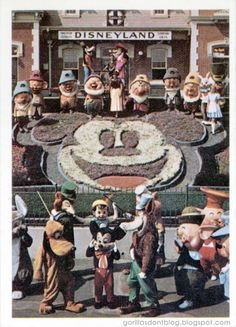 Card #39: Disney characters meet in front of Disneyland main gate with a flower portrait of Mickey Mouse.