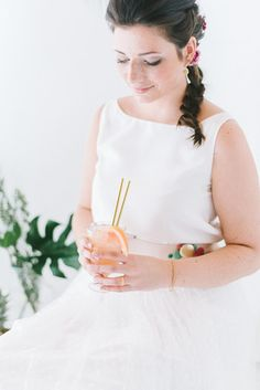 Hochzeitskleid Zweiteiler mit Crop Top und Rock aus gepunktetem Tüll und modernem Brautstrauß mit Palmzweigen und…