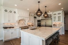 Exquisite kitchen features a pair of black cage lanterns placed over a white center island topped with white quartzite countertops fitted with an off set sink and gooseneck faucet facing the stove lined with backless gray tufted counter stools with silver nailhead trim.