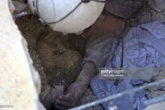 Graphic content / Jameel Mustafa Habboush, a a 13-year-old Syrian boy looks at a member of the civil defence volunteers, known as the white helmets, as they rescue him from under the rubble of a building following Russian air strikes on the rebel-held Fardous neighbourhood of the northern embattled Syrian city of Aleppo on October 11, 2016. Regime ally Russia carried out its heaviest strikes in days on Syria's Aleppo, causing massive damage in several residential areas of the city's…