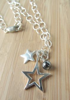 Star Necklace Silver Star Necklace Sterling Necklace by NikkiHillsDesign 'Stars and the Dark Moon' Necklace - The flat oval cable link chain necklace is made entirely from 925 sterling silver, with it's slightly hammered texture it catches the light beautifully. Your star necklace features a pendant with two silver star charms suspended, one small solid star, the other a large open star, nestled alongside a black hematite bead.