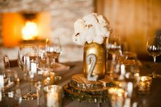 love the gold accents with the rustic elements, like the wood slices housing the centerpieces!