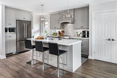 White modern kitchen with island and 3 black bar stools.