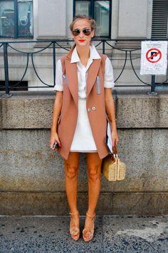 Street style look com chemise branca, colete bege, sapato e bolsa palha bege e óculos aviador.