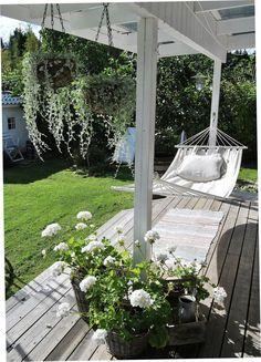 Wit gecombineerd met hout zorgt voor rust in de tuin. Ik zou het heerlijk vonden om even te dutten in mijn hangmat op de veranda.