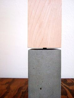 """Design: Petite Concrete Materials: Concrete. maple veneer. LED light bulb. Designer: Anna Ritchie """"My petite concrete table lamp was inspired by the functionality of it's LED light bulb. Something that is generally perceived as a cold technology has developed to mimic the warmth of nature."""""""