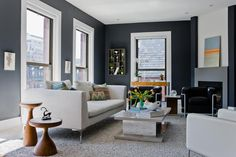 In a smallish living room, dark gray paint helps the walls fade into the background, especially when paired with light colored furniture.
