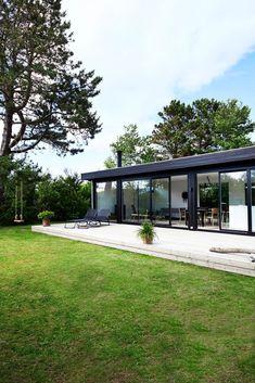 70-tallshuset er nå forvandlet til en stor og deilig hytte for hele familien. Glassfasade og flatt tak, alt innrammet i svart, gir følelsen av et moderne nybygg
