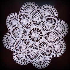 This lovely pineapple doily has real old-fashioned appeal. Around an open center is a pretty star shape. Pineapples are worked between the points of the star, and pretty fans finish off the whole, imparting a lovely scalloped edge. Measuring 14-1/2 across and crocheted in white