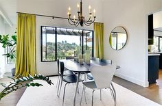 bright dining room with touch of green, supplemented by black dining table surrounded by six black white dining chairs on white rug and beautify with a black chandelier
