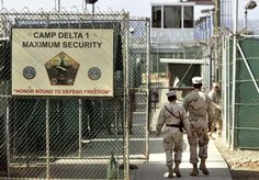 "In this June 27, 2006 file photo, reviewed by a US Department of Defense official, US military guards walk within Camp Delta military-run prison, at the Guantanamo Bay US Naval Base, Cuba. A draft executive order shows President Donald Trump asking for a review of America's methods for interrogation terror suspects and whether the U.S. should reopen CIA-run ""black site"" prisons outside the U.S."