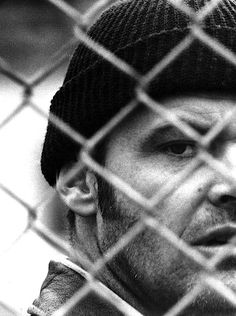 Randle McMurphy | black & white | amazing photograph | fenced in | jail | fence | shoot a look | scowl | rebel | beanie | sideburns