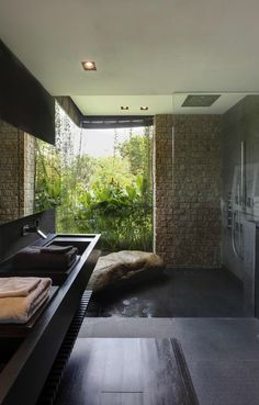 Bathroom features a large window with garden view and a sitting rock