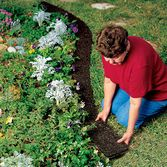 """RECYCLED RUBBER WALKWAY:  smart alternative to bark mulch, made from 100% recycled tires. A landscape backing holds the shredded rubber in place, while it also suppresses weed growth. Each 22"""" by 72"""" section is easy to install, and the 2"""" lip of fabric down one side ensures continuous coverage over wider areas."""