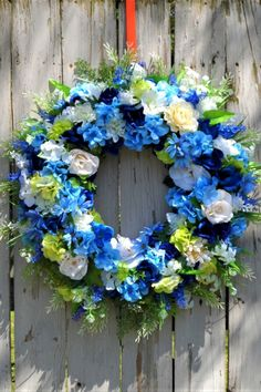 A large beautiful floral wreath for front door and indoor decorating. Foam hoop wreath form is18 inches and loaded with lots of roses, hyacinth, lilacs, daisies, lilies and hydrangea in dark blues, light blues and white. Finished item measures 24 inches. A beautiful front door and indoor decoration. Wreaths make lovely gifts for any occasion.