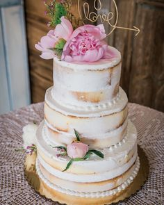 A semi-naked wedding cake adorned with pink peonies/roses for a #rusticwedding at a farm in #SouthJersey at Cecil Creek Farm #southjerseyweddings #njweddings #seminakedcakes #rusticweddingcakes #rusticweddings #farmweddings #farmweddingcakes