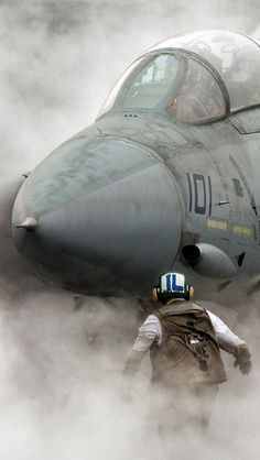 F-14 Tomcat pushing through the steam generated by the catapults. Bought to kick her of the deck! Full power... wheels up, flaps up.