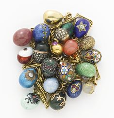 20 miniature Russian Easter egg pendants, circa 1900: 3 gem-set gold eggs; 2 gilded silver eggs with cloisonné enamel; 7 gem-set gold eggs with guilloché enamel, one August Holmström, another August Hollming; a gem-set gold egg in blue guilloché; a gold egg enameled pale green with the Hapsburg eagle; 4 gem-set or gold mounted hardstone eggs in nephrite, aventurine, and bowenite, the nephrite Eduard Schramm; a jeweled egg; a green guilloché enamel egg with jeweled mount, August Hollming.