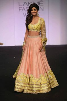 Bollywood Shilpa Shetty Raw Silk Party Wear Lehenga Choli in Peach and Yellow Colour.It comes with matching Dupatta and Bottom.It is crafted with Zari Work,Embroidery,Lace Work Design.This product can.