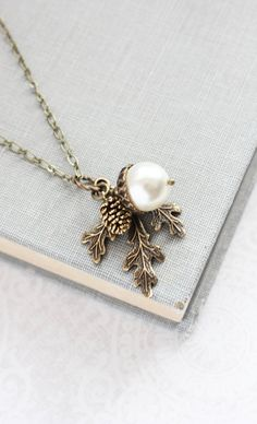 This is a beautiful nature inspired charm necklace! The charm cluster pendant includes a 12mm ivory white swarovski pearl acorn with rustic antiqued brass top, an antiqued gold pine cone with gorgeous details and a woodland branch of three leaves in antique gold brass. This is a beautiful collection of nature inspired charms and make a fun and interesting accessory for any day! The pendant measures approx. 1.5 and hangs from a nickel free antique brass chain and has a high quality lobster…
