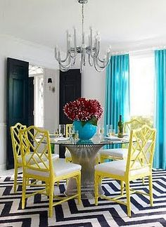 Jonathan Adler dining room with faux bamboo chairs, geometric floor pattern & metallic chrome finish on the chandelier