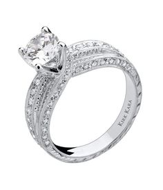 Kirk Kara Twist Solitaire Engagement Ring in 18 Karat White Gold Featuring 61 Prong Set Round White Diamonds Weighing 0.64 Carats Total Weight with Hand Engraved Details