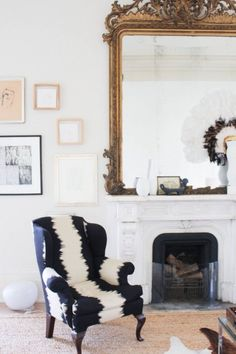 Love the oversized gold French mirror above the fireplace paired with the modern black and white chair upholstery in this stunning living room.