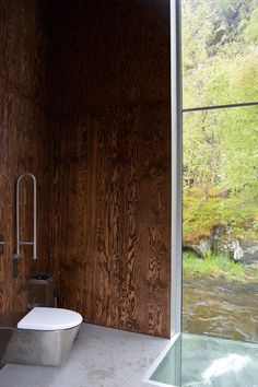 Visitors to Norway's Skjervsfossen waterfall can watch the Storelvi river rush by through a glazed floor panel in the restrooms of this service building.