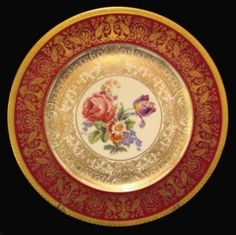 Limoges service plates. The plates feature a deep burgundy band adorned with heavy gilding, and a lovely floral scene in the center