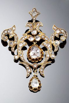 DIAMOND PENDANT/BROOCH, LATE 19TH CENTURY. Designed as an open work plaque of delicate floral and foliate motif, set throughout with rose-cut diamonds and suspending two pear-shaped rose-cut diamond drops.