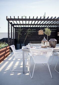 Pretty white geometric chairs and large copper planter. Black pergola.