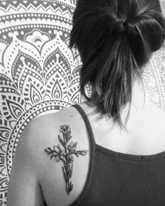 Floral cross tattoo on the back of shoulder