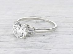 Antique Art Deco engagement ring made in platinum and centered with a GIA certified 1.55 carat old European cut diamond with H color and VVS2 clarity. Accented with three baguette diamonds on each shank. Circa 1925.See how we wear it here! A stunning solitaire with a hint of whimsey in the form of three baguette accent diamonds on each shank forming an unusual pyramid. This ring also stacks nicely with a wedding band! Diamond and gold mining has caused devastation in areas such as Africa…