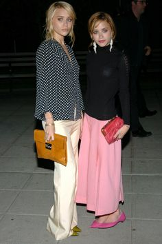 Ashley styled a business-chic ensemble — polka-dot blouse and silky wide-leg trousers with olive-green pumps and an orange leather clutch. Mary-Kate posed in a studded turtleneck, flowy pink skirt, matching kitten heels, and a hot-pink rose clutch. Mary Kate Olsen, Mary Kate Ashley, Elizabeth Olsen, Ashley Olsen Style, Olsen Twins Style, Olsen Fashion, Girl Fashion, Nicole Richie, Vanity Fair