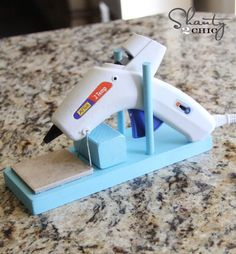 Super easy DIY hot glue gun stand. I probably have the scrap wood out in the garage. Protects your table from the hot glue and keeps the glue gun upright way better than the little wire foot on the gun.