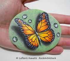 Hand painted rock with monarch butterfly and dew drops on a green font ! A great handmade painted stone made by me! Is painted on a smooth sea