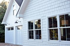 love the shingles and WHITE, garage doors that look like board and batten and those lights!