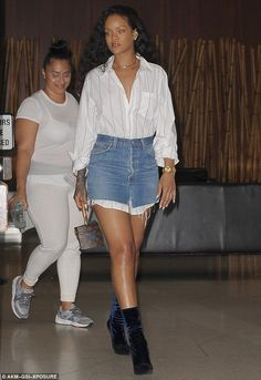 Glamorous: Rihanna was spotted in a ripped denim skirt with a striped blouse during a New York City outing with a pal on Tuesday