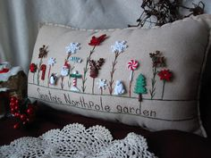 This Santa-themed hand-made muslin needlework pillow is perfect for holiday decor and celebrating the season! Size is approximately 16 x 8.