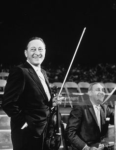 American violinist Jascha Heifetz (1901 - 1987 )(left) and American cellist Gregor Piatigorsky hold their instruments and laugh while on stage during their performance together at the Hollywood Bowl, Hollywood, California.