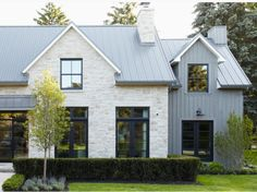 I like everything about this look: black-clad windows, stone and corrugated aluminum siding (this one is actually board  batten), this kind of metal roof. This style would look good with the simple quaking aspen and pea gravel landscape, too! I don't know how shutters would look. Window boxes would work, I'm sure.