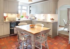 An impressive Shaker-style kitchen with a country feel. This kitchen has been designed to fit in perfectly with the original features of the fireplace and quarry tiles. The curved edges at the end of the cabinetry, the stainless steel handles, the polished quartz work surfaces add a classic charm to this space, making it feel inviting, warm and cosy