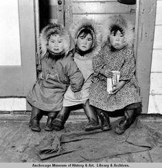 Three children wearing fur-trimmed kuspuks sitting in doorway of post office in Mekoryuk on Nunivak Island.