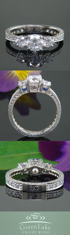 Three-stone engagement ring with engraving and accent sapphires.