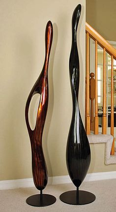 """""""Couple"""" Modern Wood Sculpture Set, Stohans Showcase.  Set of two contemporary freestanding fiber wood sculptures that are suggestive of a married couple. The taller abstract sculpture is a black lacquered ribbon like form with subtle white streaks that is heavier at the base area and gently twists with a softly pointed top. The shorter sculpture is similar but has an open area mid way up the center portion and has a deep chocolate finish with dark brown streaks."""