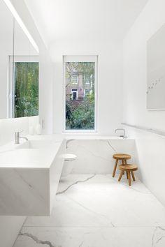 Grote witte marmeren vloerplaten  in minimalistische badkamer. Mooi hoe die adering uit het zelfde blok marmer doorlopen.