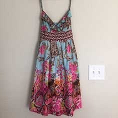 Boho adjustable scrap dress with bow Floral dress with adjustable straps and ruffle along bust. Beautiful floral fabric. Big tie to tie behind waist in contrasting fabric. Worn only a few times. Comfortable and fun dress. Excellent used condition. Fire Los Angeles Dresses Midi