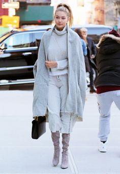Gigi Hadid wears a turtleneck, gray cape, cropped sweatpants, suede boots, and a Saint Laurent bag